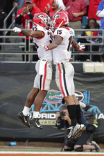 Georgia wide receiver Lawrence Cager (15) celebrates his touchdown reception against Florida with running back Brian Herrien (35) during the second half of an NCAA college football game, Saturday, Nov. 2, 2019, in Jacksonville, Fla. (AP Photo/John Raoux)
