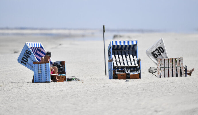 In this photo taken on Wednesday, May 15, 2019, tourists enjoy the sun in beach chairs on the car-free environmental island of Langeoog in the North Sea, Germany. Concerns about climate change have prompted mass protests across Europe for the past year and are expected to draw tens of thousands onto the streets again Friday, May 24. For the first time, the issue is predicted to have a significant impact on this week's elections for the European Parliament. (AP Photo/Martin Meissner)