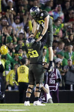 Oregon quarterback Justin Herbert celebrates after scoring with offensive lineman Penei Sewell during second half of the Rose Bowl NCAA college football game against Wisconsin Wednesday, Jan. 1, 2020, in Pasadena, Calif. (AP Photo/Marcio Jose Sanchez)