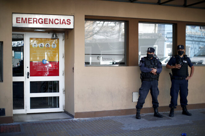 Police stand outside the hospital where former soccer star Diego Maradona is hospitalized in La Plata, Argentina Tuesday, Nov. 3, 2020. Maradona was admitted to a hospital with signs of depression Monday, three days after his 60th birthday. (AP Photo/ Natacha Pisarenko)