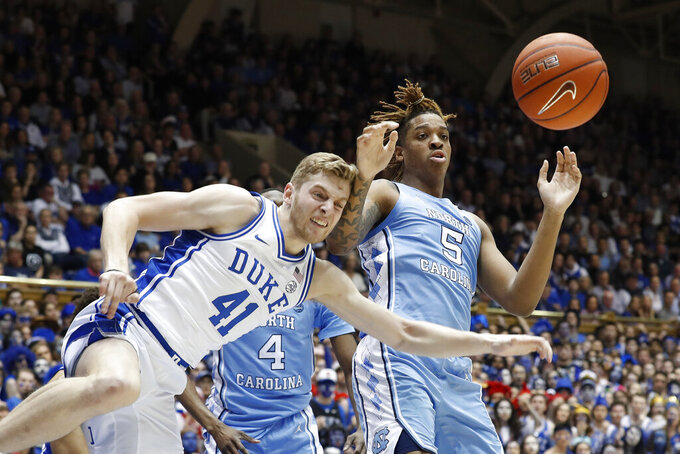 Duke forward Jack White (41) and North Carolina forward Armando Bacot (5) struggle for a rebound during the first half of an NCAA college basketball game in Durham, N.C., Saturday, March 7, 2020. (AP Photo/Gerry Broome)