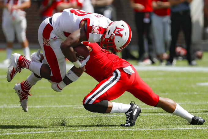 Miami of Ohio running back Tyre Shelton, left, is tackled by Cincinnati linebacker Perry Young, right, in the first half of an NCAA college football game, Saturday, Sept. 14, 2019, in Cincinnati. (AP Photo/John Minchillo)