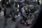 Police scuffle with Ofer Cassif, the only Jewish member of the Joint List, an alliance of Arab parties in Israel's Knesset, during a protest against planned evictions in east Jerusalem on Friday, April 9, 2021.  (AP Photo/Mahmoud Illean)
