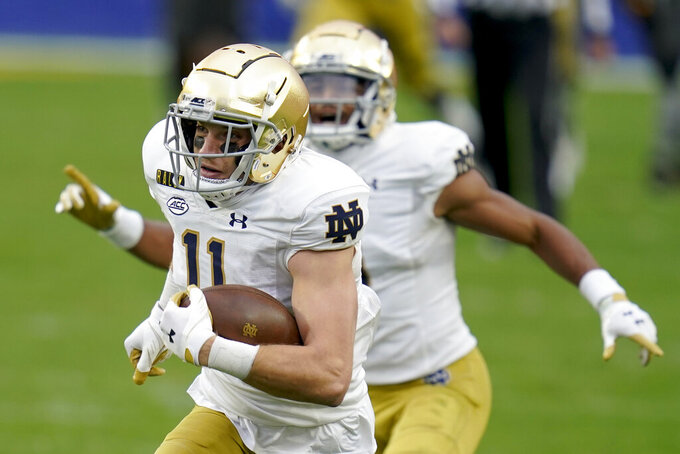 Notre Dame wide receiver Ben Skowronek, left, heads to the end zone as teammate Avery Davis (3) cheers him on after making a catch against Pittsburgh during the first half of an NCAA college football game, Saturday, Oct. 24, 2020, in Pittsburgh. (AP Photo/Keith Srakocic)