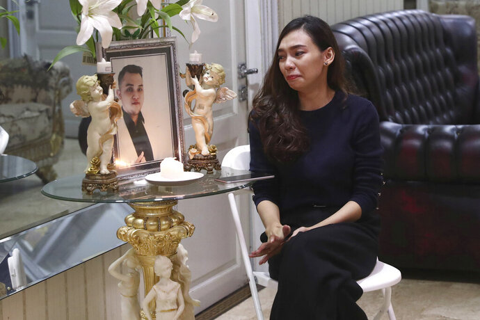 Tri Novia Septiani cries next to a portrait of her fiance Dr. Michael Robert Marampe, during an online memorial service to mark the 40th day since Marampe passed away due to COVID-19 in Jakarta, Indonesia, on June 5, 2020. Marampe knew what he wanted to be since he was a kid: a doctor and a pianist. He became both, and his passion for music even led him to Septiani - a woman he never got to marry because he got the coronavirus. Marampe became one of dozens of doctors the coronavirus has claimed so far in Indonesia. (AP Photo/Tatan Syuflana)