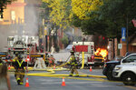 Firefighters work the scene of an explosion in downtown Sun Prairie, Wis., Tuesday, July 10, 2018. The explosion rocked the downtown area of Sun Prairie, a suburb of Madison, after a contractor struck a natural gas main Monday, sending an unknown number of people to hospitals, authorities said. (Amber Arnold/Wisconsin State Journal via AP)