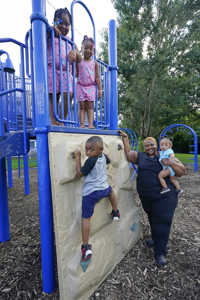 Brianne Epps of Jackson, Miss., 28, is a single mother with son Nolan Epps, 11 months in her arms, son Micah Epps, 4, left, and daughters Laila Barnes, 6, top right and Kaylee Barnes, 8, top left, at a playground at their apartment complex in Jackson, Miss., Wednesday, July 21, 2021. Epps earns $9 an hour working with infants and toddlers in a childcare center, but she has a bigger dream of operating a soul food catering business. (AP Photo/Rogelio V. Solis)