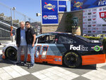 Hall of Fame driver Darrell Waltrip, left, and current NASCAR driver Denny Hamlin stand next to Hamlin's car with its throwback paint scheme at Sonoma Raceway on Friday, June 21, 2019. Hamlin revealed the paint scheme he will use at Darlington Raceway later this year to honor Waltrip, who is retiring from broadcasting this season. (AP Photo/Greg Beacham)