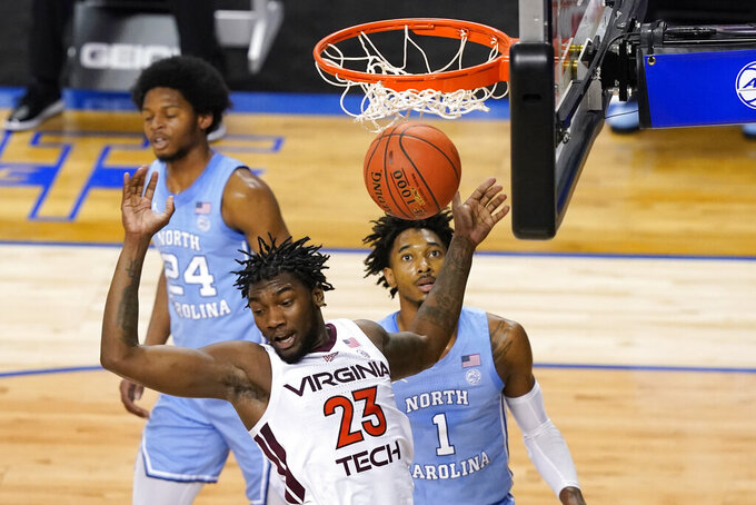 Virginia Tech guard Tyrece Radford (23) dunks over North Carolina guard Leaky Black (1) during the first half of an NCAA college basketball game in the quarterfinal round of the Atlantic Coast Conference tournament in Greensboro, N.C., Thursday, March 11, 2021. (AP Photo/Gerry Broome)