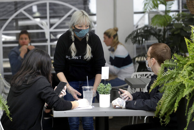 Server Katie Maloney, of Providence, R.I., center, wears a mask out of concern for the coronavirus while assisting patrons in an outdoor seating area at Plant City restaurant, in Providence, Monday, May 18, 2020. Rhode Island allowed restaurants to provide service with outdoor seated dinning Monday for the first time since the beginning of the government imposed lockdown due to the coronavirus pandemic. (AP Photo/Steven Senne)