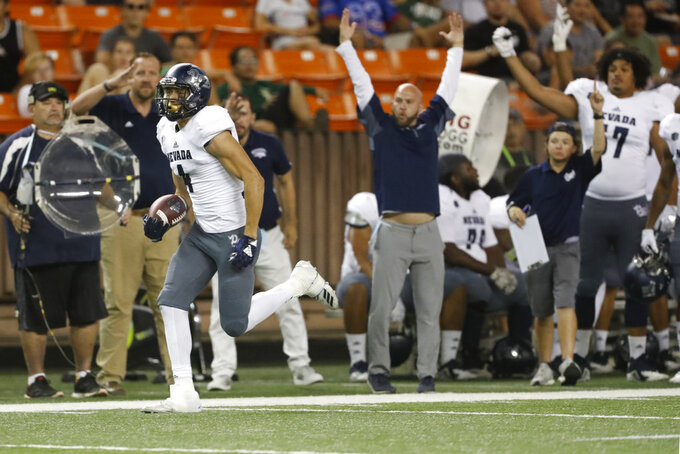 As the Nevada bench cheers, Nevada wide receiver Elijah Cooks (4) runs the ball in for a third quarter touchdown against Hawaii at an NCAA college football game Saturday, Oct. 20, 2018, in Honolulu. (AP Photo/Marco Garcia)