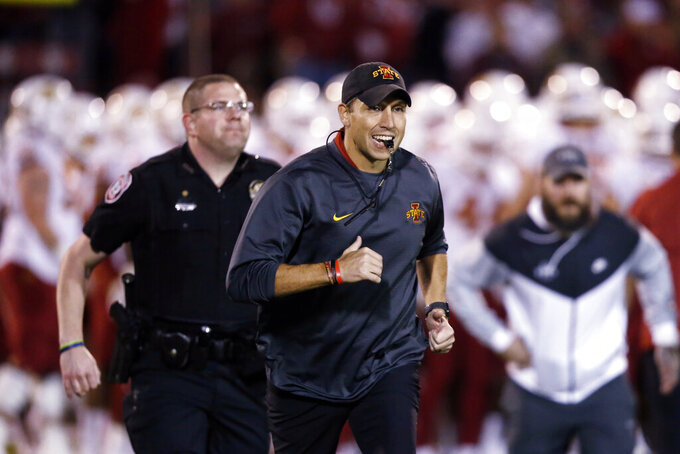 FILE - In this  Nov. 9, 2019, file photo, Iowa State head coach Matt Campbell, center, runs off the field following warm-ups before an NCAA college football game between Iowa State and Oklahoma in Norman, Okla. Iowa State has added Ball State to its 2020 home football schedule to replace the canceled Cy-Hawk Series game against Iowa. The Cyclones and Cardinals will play Sept. 12. Ball State was available because its game at Michigan was canceled as part of the Big Ten's decision to play conference games only. (AP Photo/Sue Ogrocki, File)