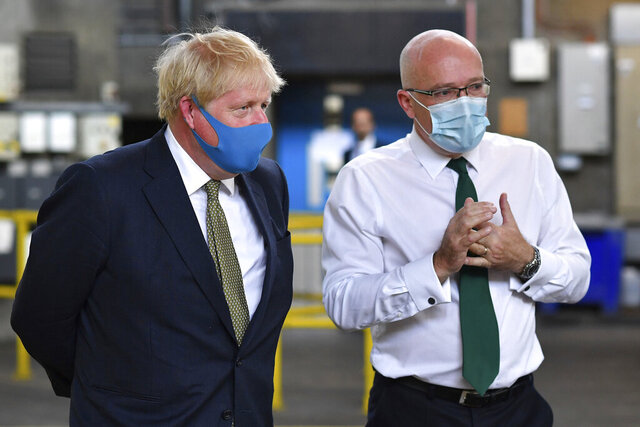Britain's Prime Minister Boris Johnson, wearing a face mask, talks with CEO London Ambulance Service Garrett Emmerson, right, during a visit to the headquarters of the London Ambulance Service NHS Trust in London, Monday July 13, 2020. (Ben Stansall/Pool via AP)