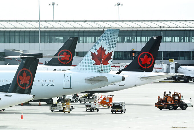FILE - In this Wednesday, Oct. 14, 2020 file photo, Air Canada planes sit on the tarmac at Pearson International airport during the COVID-19 pandemic in Toronto. On Friday, July 23, 2021, The Associated Press reported on stories circulating online incorrectly asserting Canada prohibits vaccinated pilots from flying. But Canada's transportation agency allows pilots to receive any vaccine that's been approved by the country's health regulator, Health Canada, according to Transport Canada Senior Communications Adviser Sau Sau Liu. (Nathan Denette/The Canadian Press via AP, File)