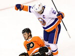 New York Islanders left wing Anders Lee (27) celebrates a teammate's goal as Philadelphia Flyers defenseman Philippe Myers (5) sits on the ice during first-period NHL Stanley Cup Eastern Conference playoff hockey game action in Toronto, Saturday, Sept. 5, 2020. (Frank Gunn/The Canadian Press via AP)