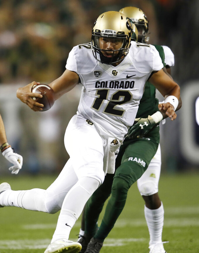 Colorado quarterback Steven Montez, front, runs past Colorado State cornerback Rashad Ajayi on the way to a touchdown in the first half of an NCAA college football game Friday, Aug. 31, 2018, in Denver. (AP Photo/David Zalubowski)