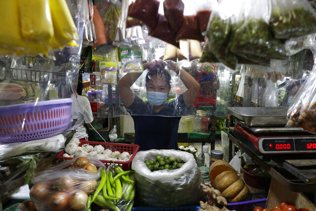 A vendor arranges her hair behind plastic sheets to curb the spread of the coronavirus at a market in Quezon city, Philippines, Tuesday, Sept. 22, 2020. Philippine President Rodrigo Duterte says he has extended a state of calamity in the entire Philippines by a year to allow the government to draw emergency funds faster to fight the COVID-19 pandemic and harness the police and military to maintain law and order. (AP Photo/Aaron Favila)