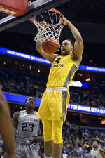 Marquette forward Theo John (4) dunks against Georgetown forward Josh LeBlanc (23) during the first half of an NCAA college basketball game, Tuesday, Jan. 15, 2019, in Washington. (AP Photo/Nick Wass)