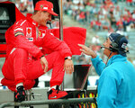 FILE - In this July 25, 1997, file photo, Germany's Michael Schumacher, left, of the Ferrari team, shares a joke with Benetton chief Flavio Briatore, right, at the start of the first free practice session for the upcoming German Formula 1 Grand Prix in Hockenheim. Against the backdrop of celebrations marking Michael Schumacher's 50th birthday Thursday, Jan. 3, 2019, the medical condition of Formula One's most successful driver remains just as fiercely guarded by his close family. (AP Photo/Thomas Kienzle, File)