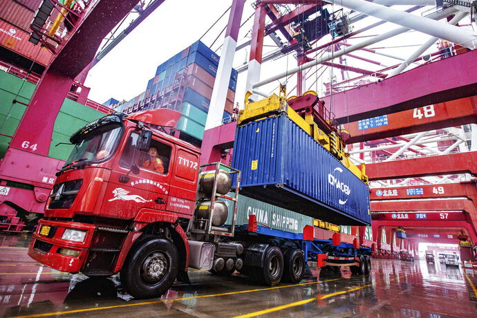 A worker waits to transport containers at the container port in Qingdao in eastern China's Shandong province on Tuesday, Jan. 14, 2020. China's exports rose 0.5% in 2019 despite a tariff war with Washington after growth rebounded in December on stronger demand from other markets. (Chinatopix Via AP)