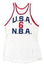 This photo provided by Hunt Auctions, shows a No. 6 USA basketball jersey which was worn by Bill Russell. The most-decorated man in NBA history will soon be giving the public a chance to own some of the prized artifacts from his legendary basketball career. Hall of Famer Bill Russell announced, Thursday, July 22, 2021, that he is offering hundreds of items from his personal collection including trophies, rings, basketballs, jerseys, letters, photos, and other memorabilia at auction. (Mike Freeberg/Hunt Auctions via AP)