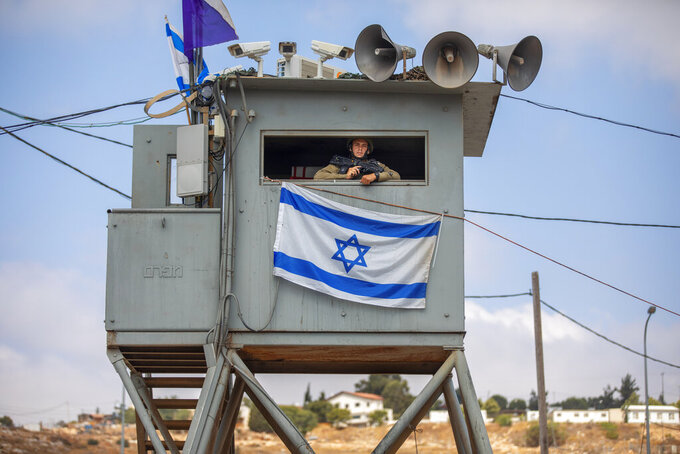 An Israeli soldier stands guard at the Tapuach junction next to the West Bank city of Nablus, Tuesday, June 30, 2020. Israeli Prime Minister Benjamin Netanyahu appears determined to carry out his pledge to begin annexing parts of the occupied West Bank, possibly as soon as Wednesday. (AP Photo/Oded Balilty)