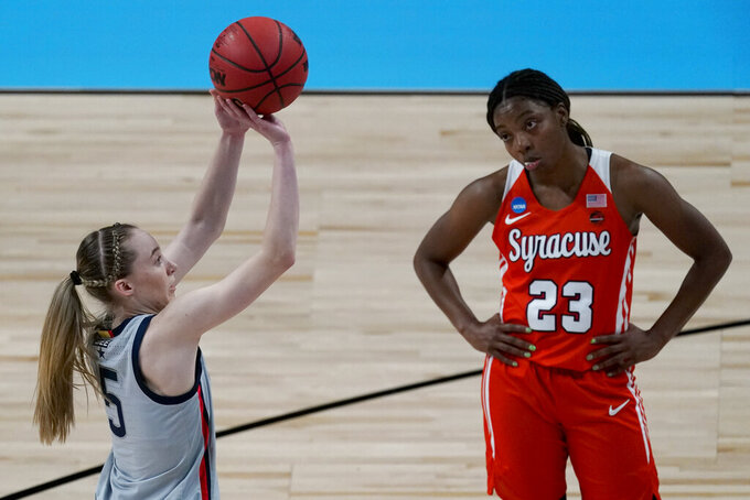 Syracuse guard Kiara Lewis (23) watches while UConn guard Paige Bueckers (5) shoots a free throw during the first half of a college basketball game in the second round of the women's NCAA tournament at the Alamodome in San Antonio, Tuesday, March 23, 2021. (AP Photo/Charlie Riedel)