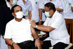 A health worker administers second dose of the AstraZeneca COVID-19 vaccine to Thailand's Prime Minister Prayuth Chan-ocha, left, at Bamrasnaradura Infectious Diseases Institute in Bangkok, Thailand, Monday, May 24, 2021. (Government Spokesman Office via AP)