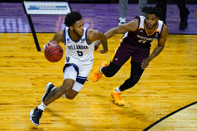Villanova guard Justin Moore (5) drives on Winthrop guard Charles Falden (11) in the first half of a first round game in the NCAA men's college basketball tournament at Farmers Coliseum in Indianapolis, Friday, March 19, 2021. (AP Photo/Michael Conroy)