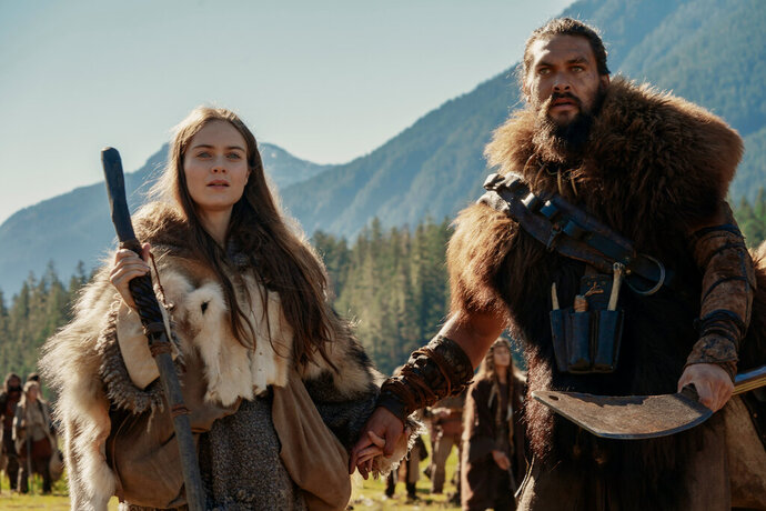 This image released by Apple TV Plus shows Jason Momoa, right, and Hera Hilmar in a scene from