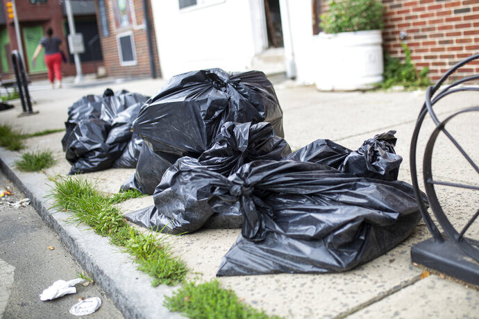 In this photo from July 17, 2020, trash left to be picked up is on the sidewalk in the Fishtown neighborhood of Philadelphia along Frankford Avenue. The city's 311 complaint line has received 9,753 calls about trash and recycling as of July 29 compared to 1,873 in February. (Tyger Williams/The Philadelphia Inquirer via AP)