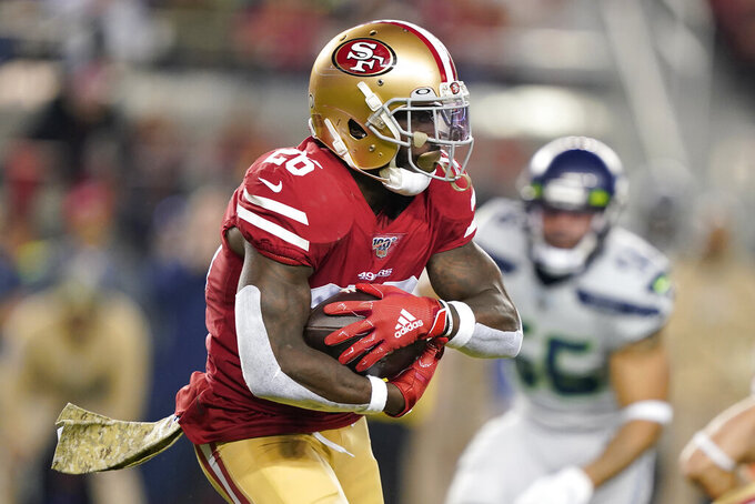 San Francisco 49ers running back Tevin Coleman (26) runs against the Seattle Seahawks during the first half of an NFL football game in Santa Clara, Calif., Monday, Nov. 11, 2019. (AP Photo/Tony Avelar)