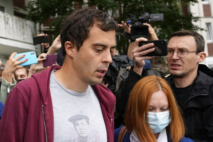 """Roman Dobrokhotov, chief editor of The Insider walks surrounded police officers and journalists, in Moscow, Russia, Wednesday, July 28, 2021.  Police in Russia raided the home of the chief editor of an investigative media outlet that was recently designated as a """"foreign agent,"""" the latest step by authorities to raise pressure on independent media ahead of the country's September parliamentary election. (AP Photo/Alexander Zemlianichenko)"""