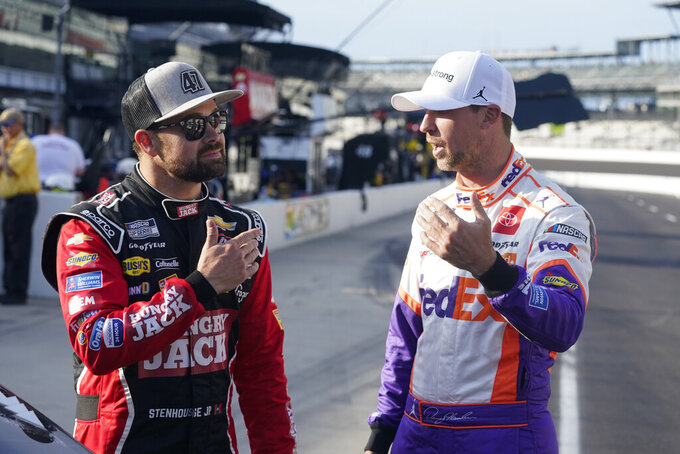 Ricky Stenhouse Jr., left, talks with Denny Hamlin before qualifications for the NASCAR Series auto race at Indianapolis Motor Speedway, Sunday, Aug. 15, 2021, in Indianapolis. (AP Photo/Darron Cummings)