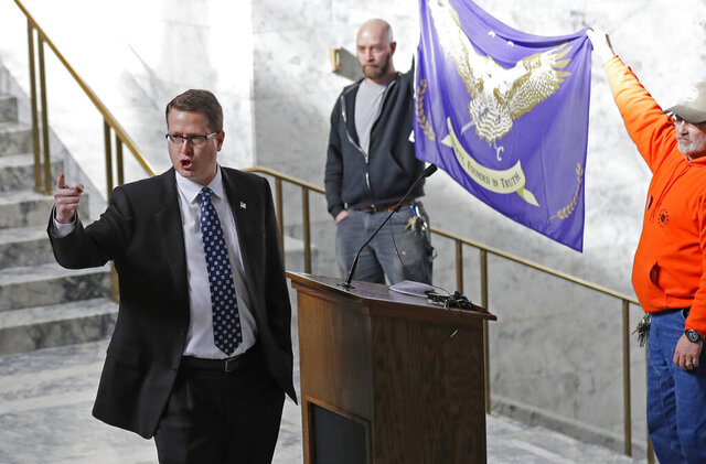 FILE - In this Friday, Feb. 15, 2019 file photo, Washington state Rep. Matt Shea, R-Spokane Valley, gestures as he gives a speech in front of the liberty state flag at the Capitol in Olympia, Wash., during a rally held by people advocating splitting Washington state into two separate states and questioning the legality of Washington's I-1639 gun-control measure. Prominent state lawmaker Shea says the coronavirus is a foreign bio-weapon and claims Marxists are using the pandemic to advance totalitarianism. (AP Photo/Ted S. Warren, File)