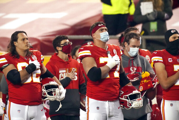 Kansas City Chiefs players stand on the field during the national anthem before the AFC championship NFL football game against the Buffalo Bills, Sunday, Jan. 24, 2021, in Kansas City, Mo. (AP Photo/Charlie Riedel)