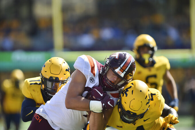 Virginia Tech Hokies tight end Drake DeIuliis (89) is tackled by West Virginia Mountaineers safety Alonzo Addae (4) during the second half of  an NCAA college football game in Morgantown, W.Va., Saturday, Sept. 18, 2021. (AP Photo/William Wotring)