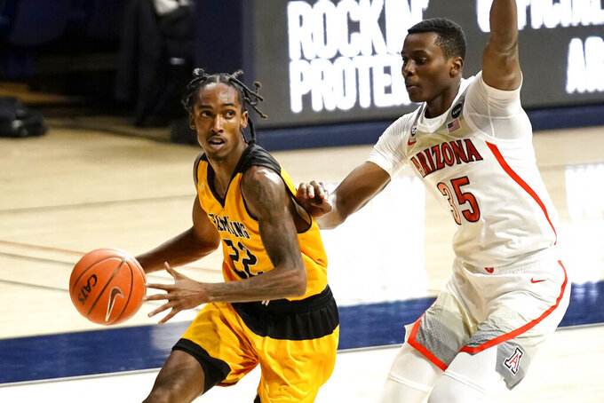 Grambling guard Prince Moss drives on Arizona center Christian Koloko (35) during the first half of an NCAA college basketball game Friday, Nov. 27, 2020, in Tucson, Ariz. (AP Photo/Rick Scuteri)