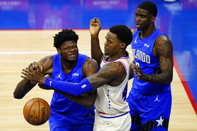 Orlando Magic's Mo Bamba, left, cannot get a shot past Philadelphia 76ers' Paul Reed, center, as Dwayne Bacon looks on during the second half of an NBA basketball game, Sunday, May 16, 2021, in Philadelphia. (AP Photo/Matt Slocum)