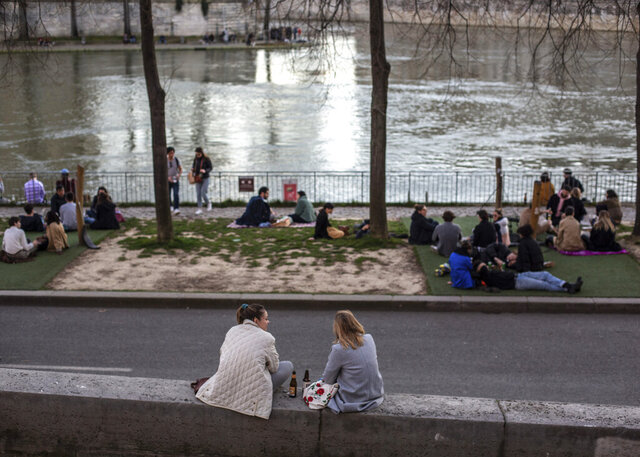 FILE - In this March 15, 2020 file photo, people stroll along the Seine river banks at sunset in Paris. Like so many catastrophes before the coronavirus pandemic, memories are settling in of the