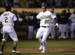 Oakland Athletics' Mark Canha, right, celebrates with Khris Davis (2) after scoring against the Kansas City Royals during the seventh inning of a baseball game Tuesday, Sept. 17, 2019, in Oakland, Calif. (AP Photo/Ben Margot)