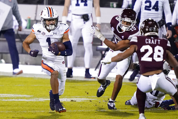 Auburn wide receiver Anthony Schwartz (1) runs with a reception past Mississippi State defenders for a first down during the first half of an NCAA college football game Saturday, Dec. 12, 2020, in Starkville, Miss. (AP Photo/Rogelio V. Solis)