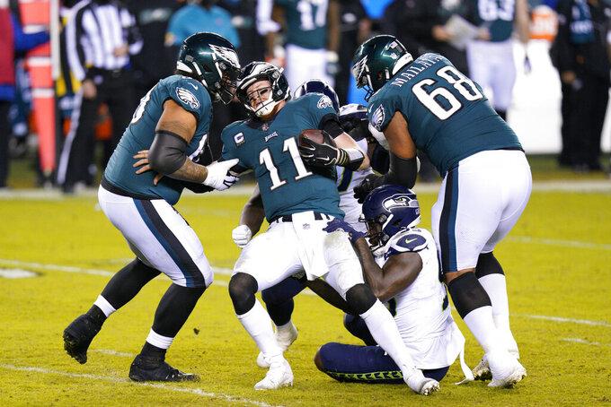 Philadelphia Eagles' Carson Wentz (11) is sacked by Seattle Seahawks' Benson Mayowa (95) during the second half of an NFL football game, Monday, Nov. 30, 2020, in Philadelphia. (AP Photo/Chris Szagola)