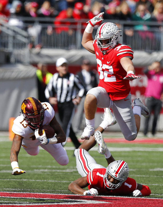 Minnesota receiver Rashod Bateman, left, is brought down by Ohio State defensive back Jeffrey Okudah, bottom, as linebacker Tuf Borland follows the play during the second half of an NCAA college football game Saturday, Oct. 13, 2018, in Columbus, Ohio. Ohio State beat Minnesota 30-14. (AP Photo/Jay LaPrete)