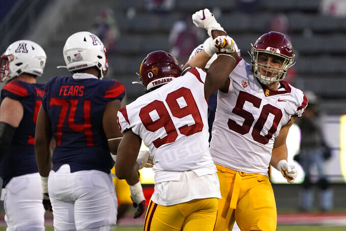 Southern California's Drake Jackson (99) and Nick Figueroa (50) celebrate after USC defeated Arizona 34-30 in an NCAA college football game, Saturday, Nov. 14, 2020, in Tucson, Ariz. (AP Photo/Rick Scuteri)