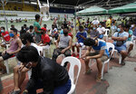 Men who got arrested for violating quarantine health protocols wait for their turn at the Amoranto Sports Complex in metropolitan Manila, Philippines on Wednesday, July 8, 2020. Philippine President Rodrigo Duterte eased one of the world's longest lockdowns in the Philippine capital of more than 13 million people on June 1 after the economy shrank in the first quarter in its first contraction in more than two decades. (AP Photo/Aaron Favila)