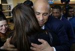 U.S. Sen. Cory Booker, D-N.J., center right, embraces a person in the audience after making remarks during a campaign stop, Sunday, Feb. 17, 2019, in Manchester, N.H. (AP Photo/Steven Senne)
