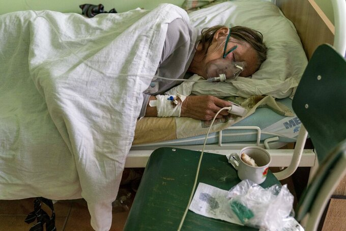 A patient with coronavirus breathes with an oxygen mask in a hospital intensive care unit in Stryi, Ukraine, on Tuesday, Sept. 29, 2020. Coronavirus infections in Ukraine began surging in late summer, and the ripples are hitting towns in the western part of the country. The government wants to avoid imposing a new lockdown, but officials acknowledge that the rising infections could make it necessary. (AP Photo/Evgeniy Maloletka)