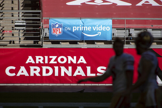 "FILE - In this Saturday, Dec. 26, 2020, file photo, An 'NFL on prime video' banner hangs on the field prior to an NFL football game between the San Francisco 49ers and Arizona Cardinals in Glendale, Ariz. The NFL will nearly double its media revenue to more than $10 billion a season with new rights agreements announced Thursday, March 18, 2021 including a deal with Amazon Prime Video that gives the streaming service exclusive rights to ""Thursday Night Football"" beginning in 2022.(AP Photo/Jennifer Stewart, File)"