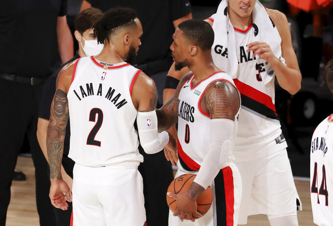 Portland Trail Blazers' Gary Trent Jr.(2) and Damian Lillard (0) react after defeating the Memphis Grizzlies in overtime of an NBA basketball game Friday, July 31, 2020, in Lake Buena Vista, Fla. (Mike Ehrmann/Pool Photo via AP)